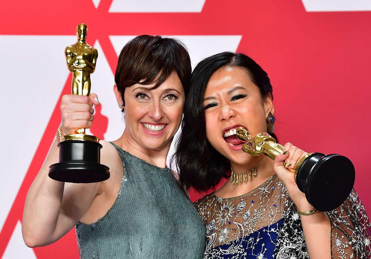 """Best Animated Short Film winners for """"Bao"""" Domee Shi (R) and Becky Neiman-Cobb pose in the press room with their Oscars during the 91st Annual Academy Awards at the Dolby Theatre in Hollywood, California on February 24, 2019."""