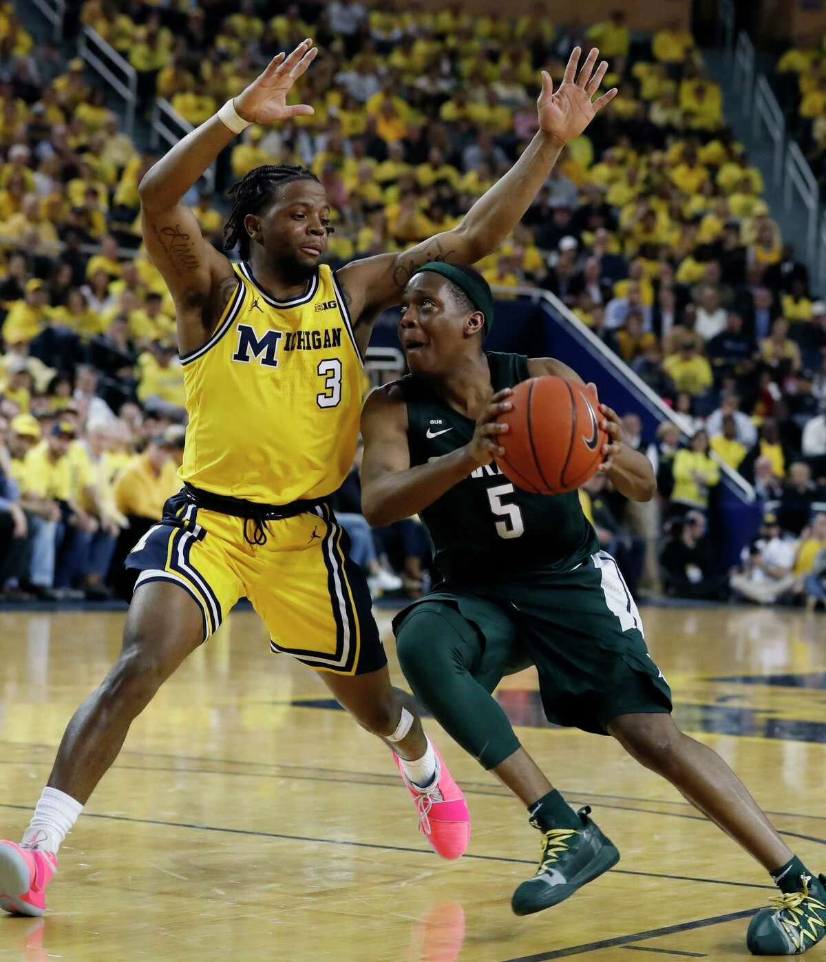 Michigan State guard Cassius Winston (5) drives on Michigan guard Zavier Simpson (3) during the second half of an NCAA college basketball game, Sunday, Feb. 24, 2019, in Ann Arbor, Mich. (AP Photo/Carlos Osorio)