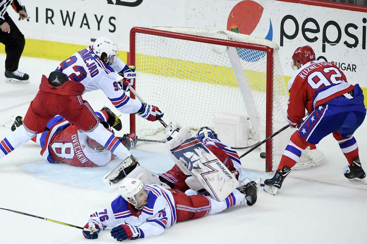 Washington Capitals center Evgeny Kuznetsov (92), of Russia, scores the game-winning goal during overtime of an NHL hockey game against New York Rangers center Mika Zibanejad (93), defenseman Brady Skjei (76), and goaltender Henrik Lundqvist, second from right, , of Sweden, Sunday, Feb. 24, 2019, in Washington. Also seen is Capitals left wing Alex Ovechkin (8), , of Russia. The Capitals won 6-5 in overtime. (AP Photo/Nick Wass)