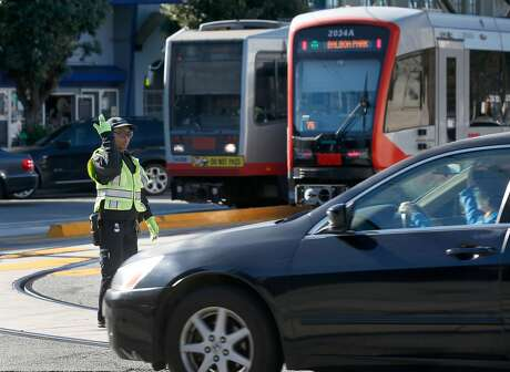 Mercede Travis directs traffic in front of the West Portal Muni station in San Francisco, Calif. on Friday, Feb. 22, 2019. Traffic officers have been assigned to the intersection of West Portal Avenue and Ulloa Street for the past few weeks to control the often congested flow of cars, trucks, buses and streetcars.