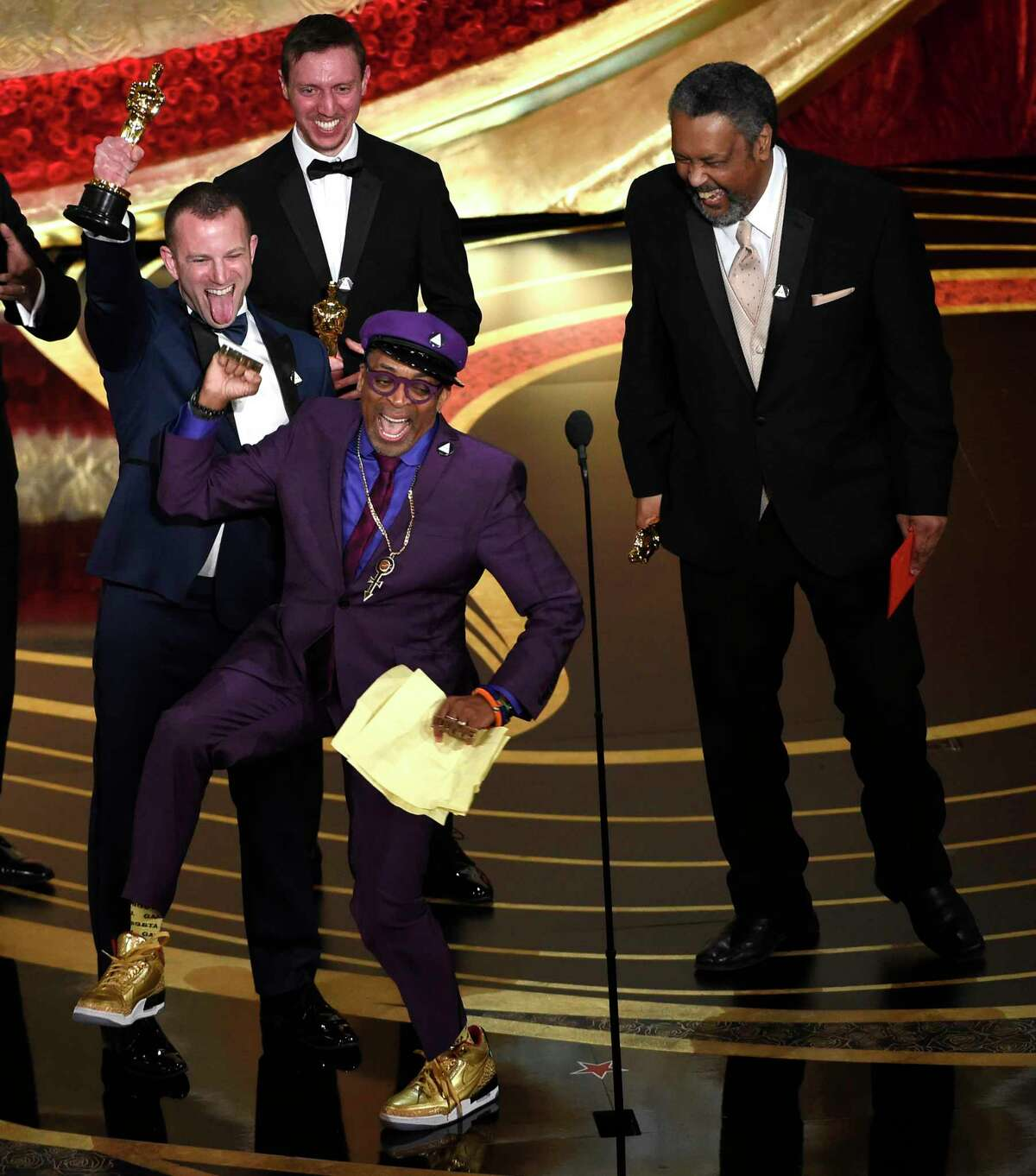 Spike Lee, foreground center, Charlie Wachtel, from left, David Rabinowitz and Kevin Willmott accept the award for best adapted screenplay for