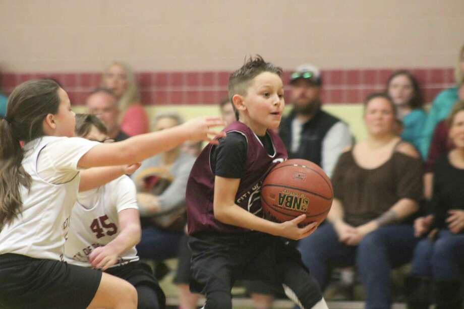 Cam Gonzalez drives hard to the basket, looking for one of his five buckets he scored in Sunday night's 8U city championship game at the Earl Dunn Gym. Photo: Robert Avery
