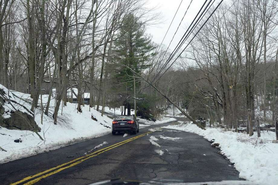 FILE PHOTO A motorist passes under a falling tree supported by wires along Wildwood Road in North Stamford, Conn. on Thursday, March 8, 2018. Photo: Matthew Brown / Hearst Connecticut Media / Stamford Advocate