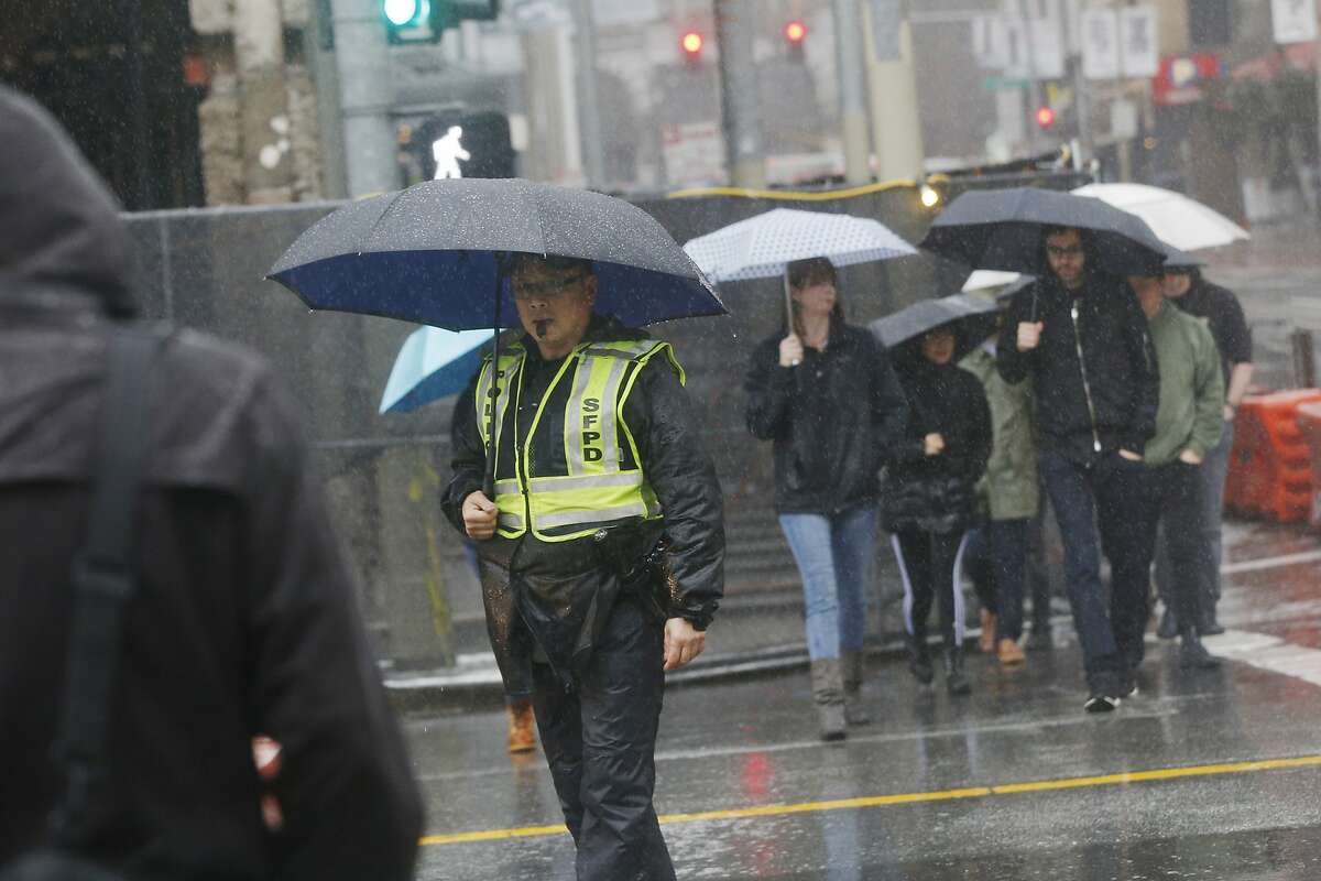 Officer Eddie Wu works in the rain directing traffic in the intersection of Mission and Third Streets on Wednesday, February 13, 2019 in San Francisco, Calif.