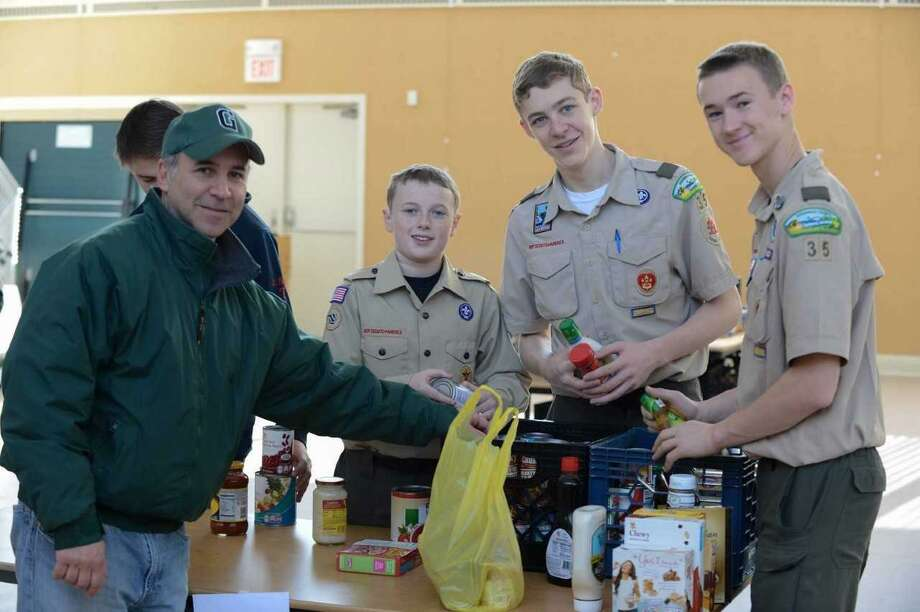 State Rep. Fred Camillo, assists Boy Scouts during Scouting for Food drive to benefit Neighbor to Neighbor in Greenwich. Photo: Contributed /