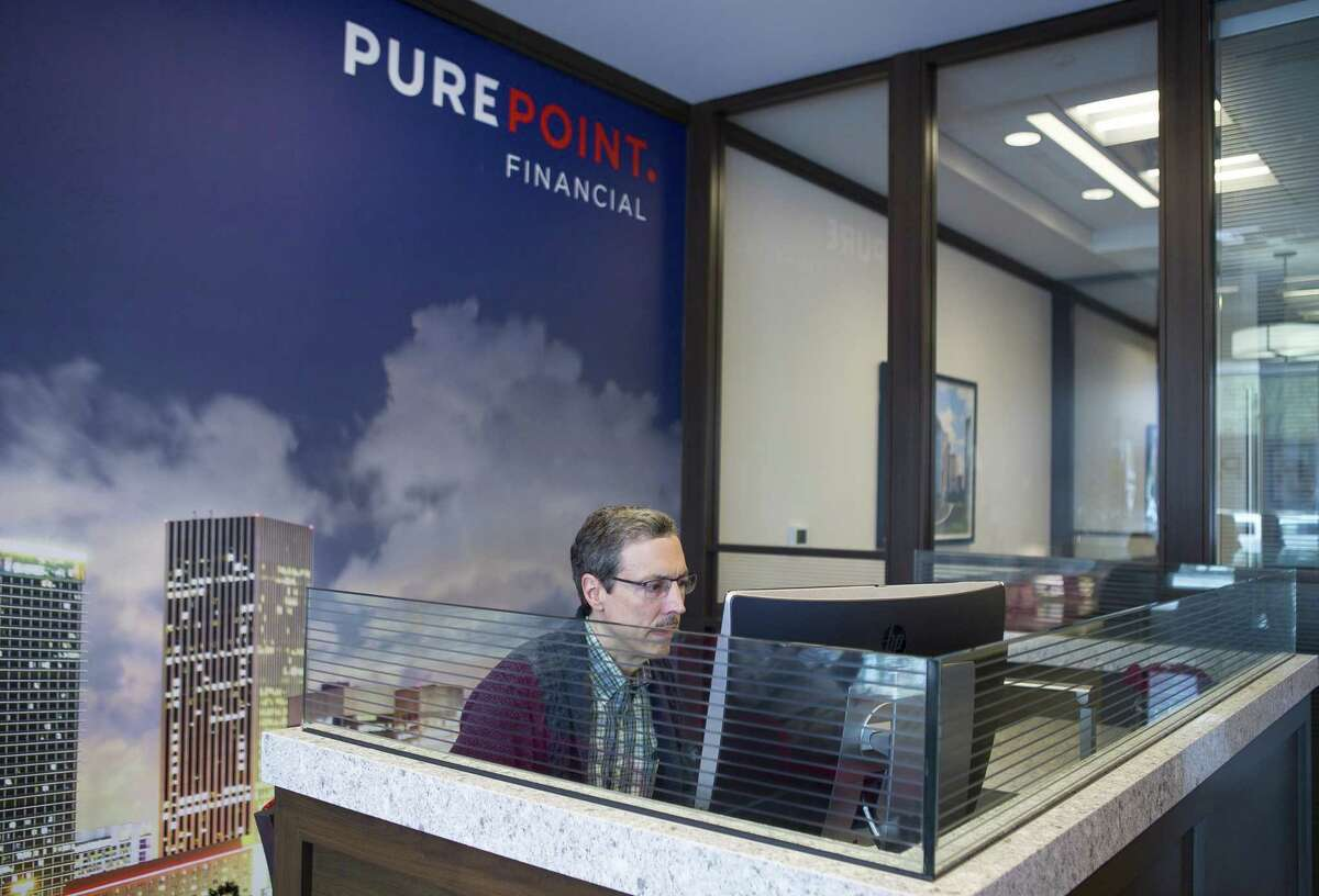 Howard Maple checks his account balance at PurePoint Financial in the Galleria area of Houston. Maple is self-employed and uses PurePoint for his savings account.