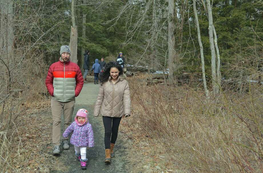 Making the 1.5-mile trek are Justin Kristof of Beacon Falls, Katherine Lopez of Fairfield and her daughter, Milena, 2, at the Fairfield Audubon Center's Winter Walk on Saturday, Feb. 23, 2019, in Fairfield, Conn. Photo: Jarret Liotta / For Hearst Connecticut Media / Fairfield Citizen News Freelance