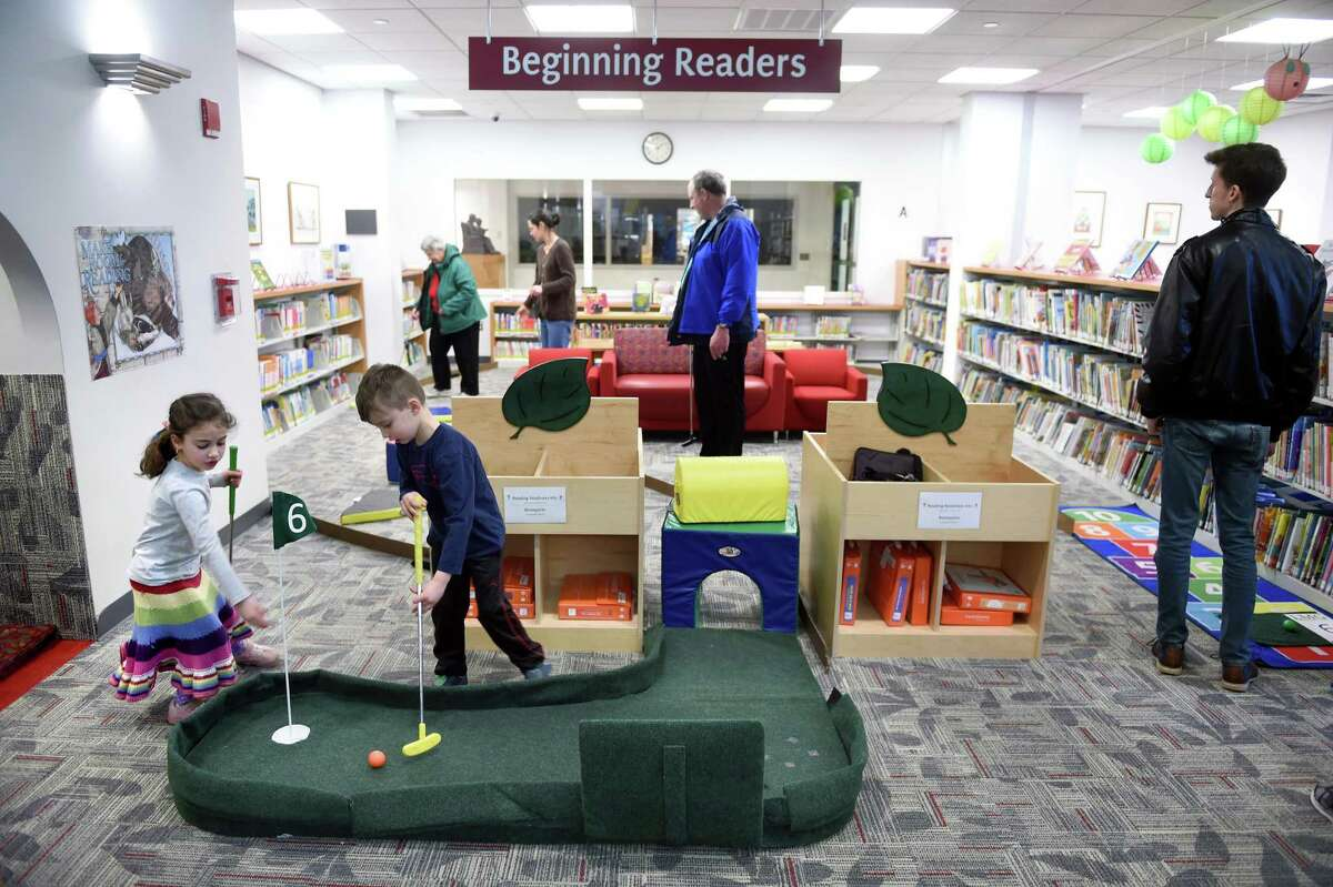 Hazel Martin (far left), 5, and her twin brother, Jed (left), of Wallingford play Mini Golf inside the Wallingford Public Library on February 24, 2019. The two-day Mini Golf event raised money for the creation of the Wonder Room inside the Children's Library. The room will feature a mini-makerspace, a baby and toddler program space, and furnishings for students and families.