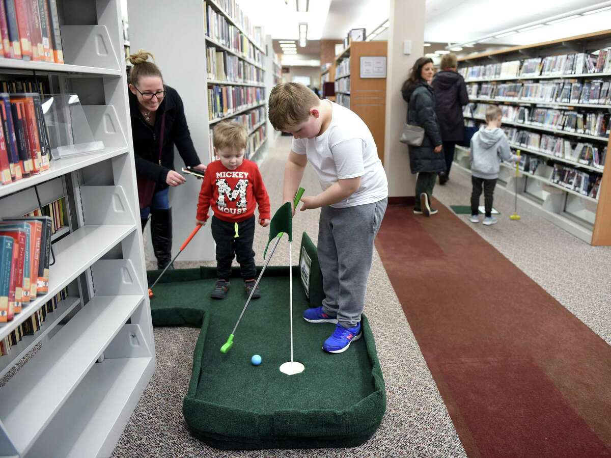 From left, Shanielle Antonelli of Wallingford watches her children, Dylan, 2, and Brayden, 6, play Mini Golf inside the Wallingford Public Library on February 24, 2019. The two-day Mini Golf event raised money for the creation of the Wonder Room inside the Children's Library. The room will feature a mini-makerspace, a baby and toddler program space, and furnishings for students and families.