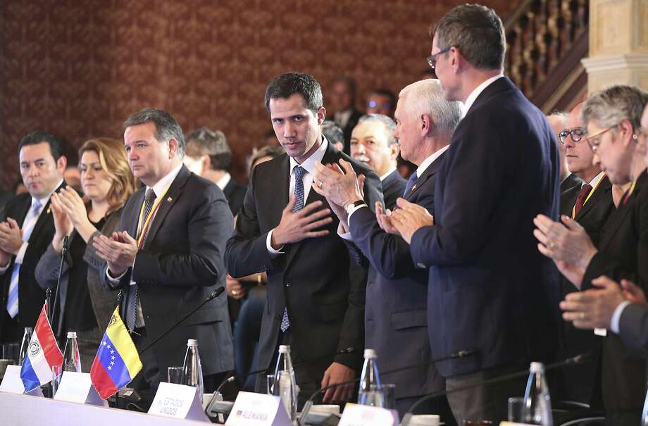 Flanked by Vice President Mike Pence, right center, Venezuela's self-proclaimed interim president Juan Guaido, acknowledges the applause during a meeting of the Lima Group concerning Venezuela at the Foreign Ministry in Bogota, Colombia, Monday, Feb. 25, 2019. Pence arrived in the Colombian capital for an emergency summit of regional leaders to discuss Venezuela's crisis and immediately met with Guaido. In a speech to the group, Pence urged regional partners to freeze oil assets controlled by Maduro, transfer the proceeds to Guaido and restrict visas for Maduro's inner circle. (AP Photo/Martin Mejia) Photo: Martin Mejia / Associated Press