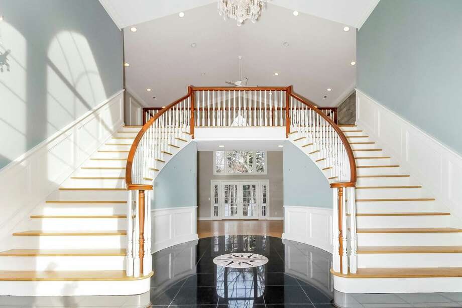 Double-doors open into a grand two-story entry, which boasts a decorative and sweeping staircase that highlights the elegant tone that is carried throughout the home's 5,095 square feet. The four-bedroom home at 4 Herrmann Lane in Easton is listed for $699,900. Photo: William Raveis / ONLINE_CHECK