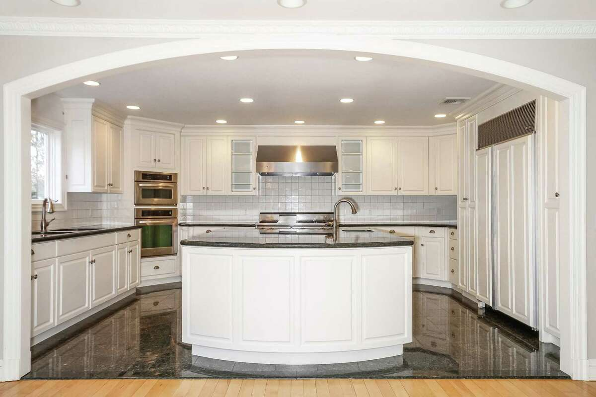 The gourmet kitchen at 4 Herrmann Lane in Easton features stainless steel appliances, custom white cabinets, granite countertops and a built-in barbecue.