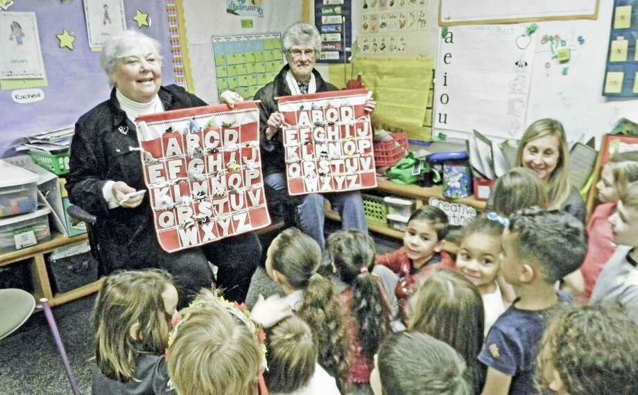 From left, Sharon Sheedy and Ann Vecchito Anderson, members of the Church of the Holy Trinity on Main Street in Middletown, demonstrate how to use the ABC Wall Charts in the kindergarten classroom of Judy David. Photo: Contributed Photo