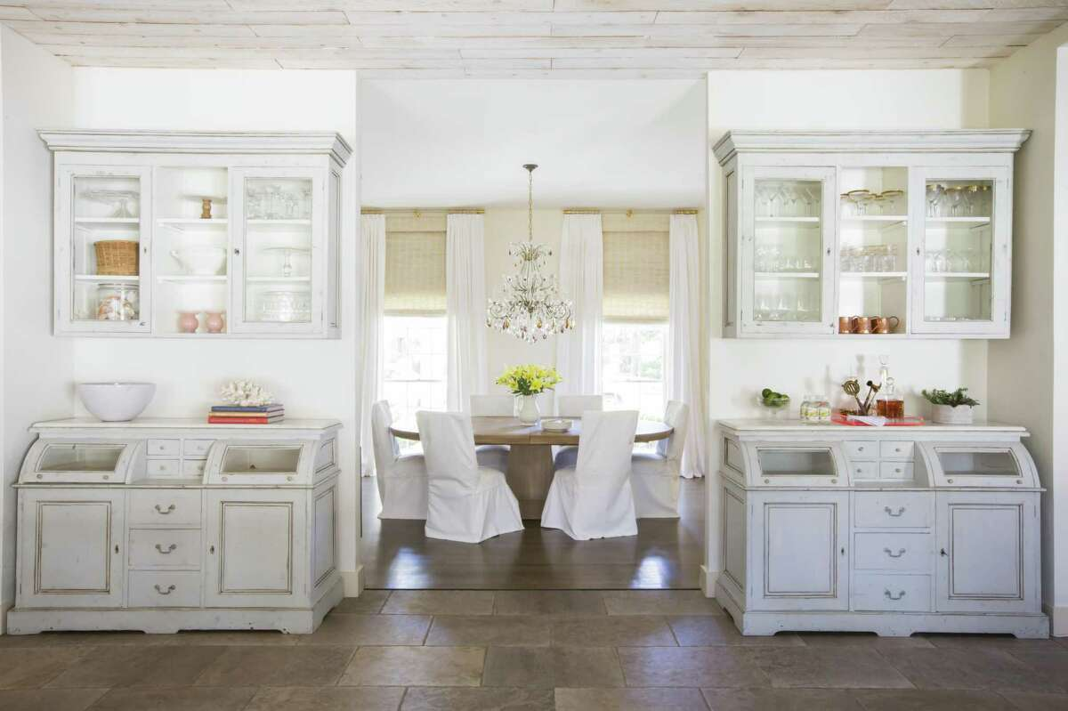 A simple palette created a pleasant space for a family who wanted casual but elegant surroundings. Slip-covered chairs surround a more rustic table and a pretty chandelier amps up the glamour in the room. Leading into the dining room, matching cabinets show off crystal and other tabletop items.