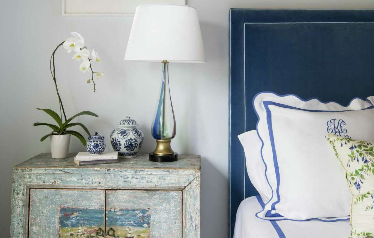 Monogrammed bedding in a cheerful blue and a long-blooming white orchid add classic touches to this master bedroom.