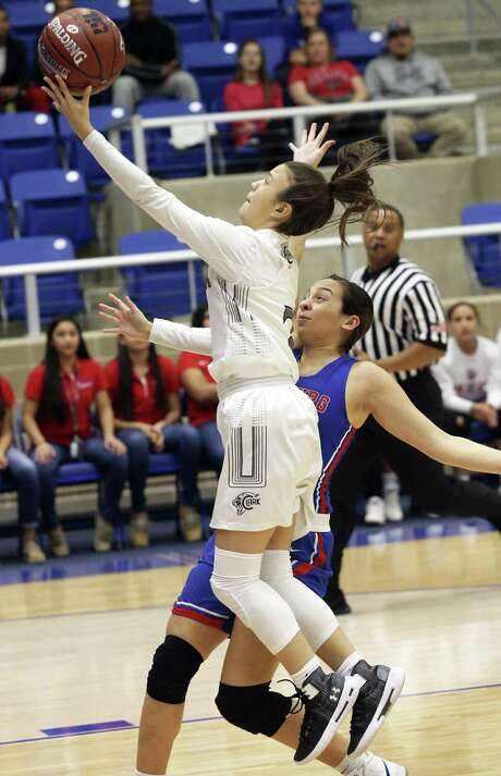 Cougar guard Sydney Solitaire scoops a layup after beating Alyssa Jade Salinas to the paint as Clark plays Edinburg in the Region IV-6A girls basketball tournament at Northside Gym on February 22, 2019. Photo: Tom Reel, Staff / Staff Photographer / 2019 SAN ANTONIO EXPRESS-NEWS