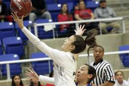 Cougar guard Sydney Solitaire scoops a layup after beating Alyssa Jade Salinas to the paint as Clark plays Edinburg in the Region IV-6A girls basketball tournament at Northside Gym on February 22, 2019.