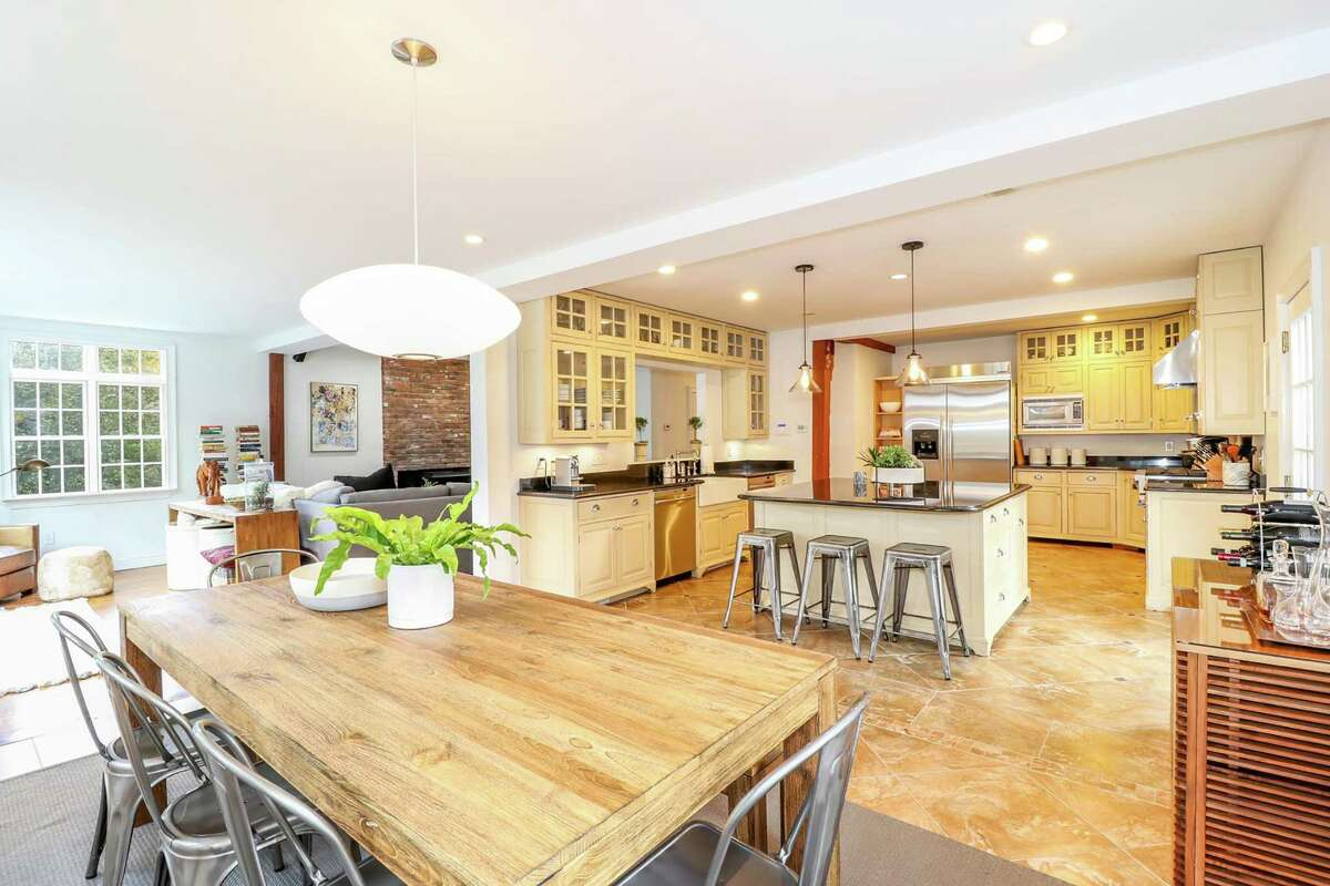 The kitchen features custom cabinetry, granite counters, pendant and recessed lighting, a farmhouse-style sink and a large center island.