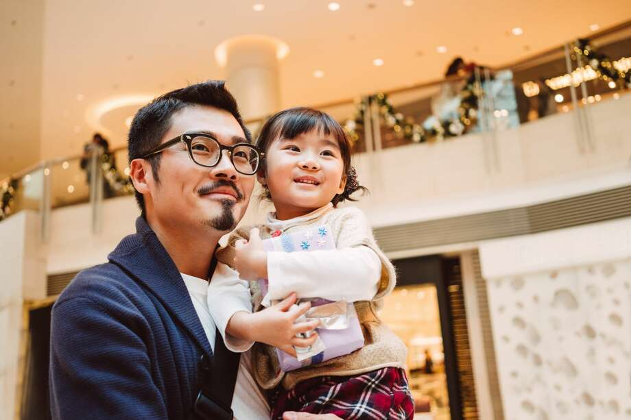 A father is questioned by security when he brings his daughter with him to the mall. Photo: Images By Tang Ming Tung/Getty Images