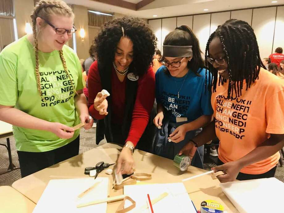 ExxonMobil Environmental Engineer Shawn Simmons works with three eighth-grade students at this year's festival celebrating National Introduce a Girl to Engineering Day. Photo: Courtesy Photos / Courtesy Photos