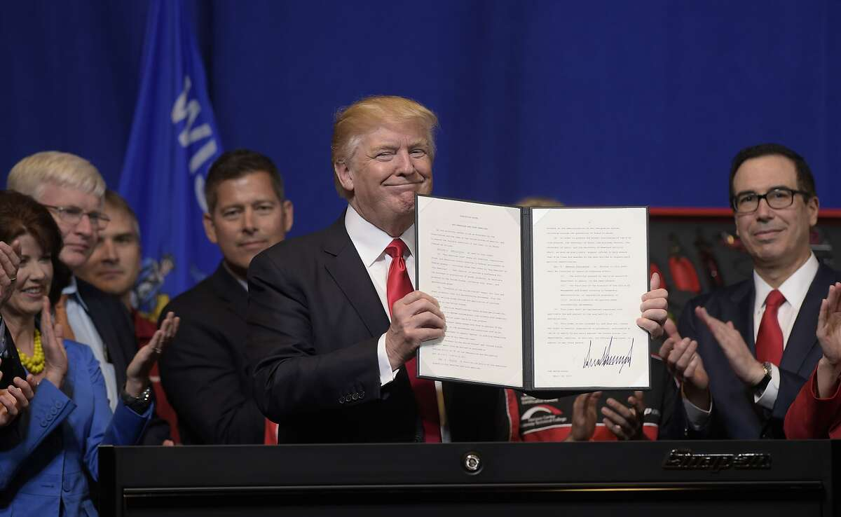 FILE - In this April 18, 2017 file photo, President Donald Trump holds up the