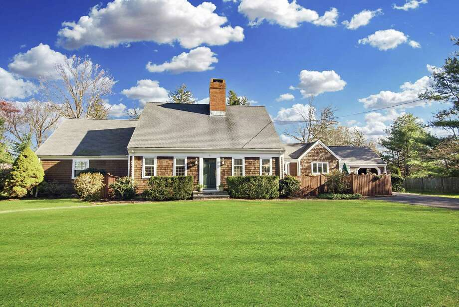 The brown shingle Cape Cod-style house at 158 Redding Road sits on a one-acre property in Greenfield Hill.