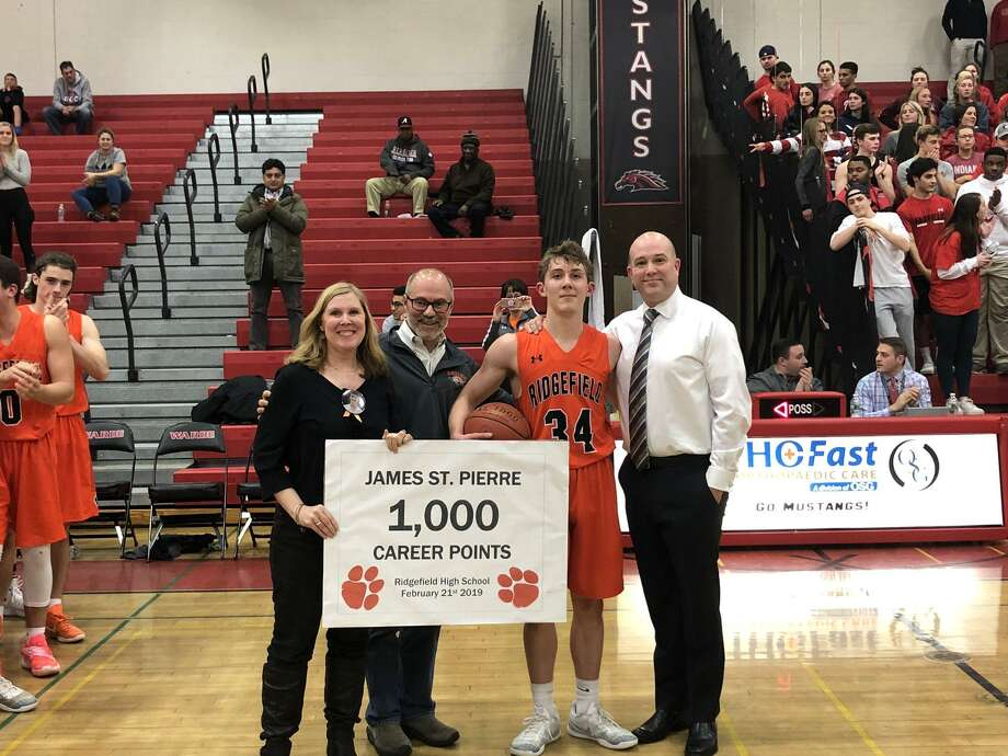 James St. Pierre was honored after scoring his 1,000th career point during Ridgefield's game at Fairfield Warde. Photo: Contributed Photo