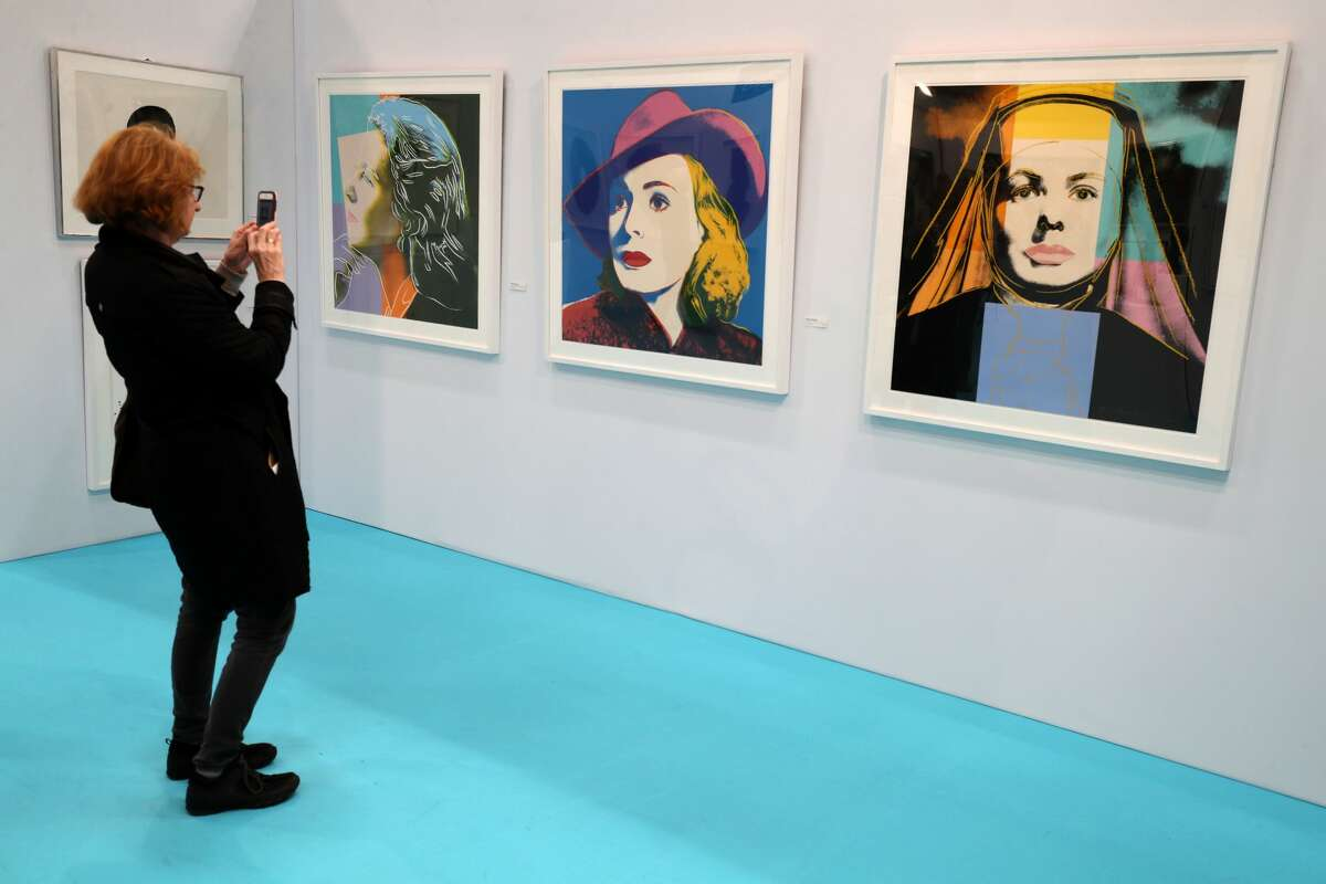 A woman takes a picture of a rare iconic collection of Ingrid Bergman prints by Andy Warhol. The Bergman portfolio consists of 'Herself' (left), 'Bergman with Hat' (centre) and 'Ingrid The Nun' at the Art Source art show at the RDS in Dublin.