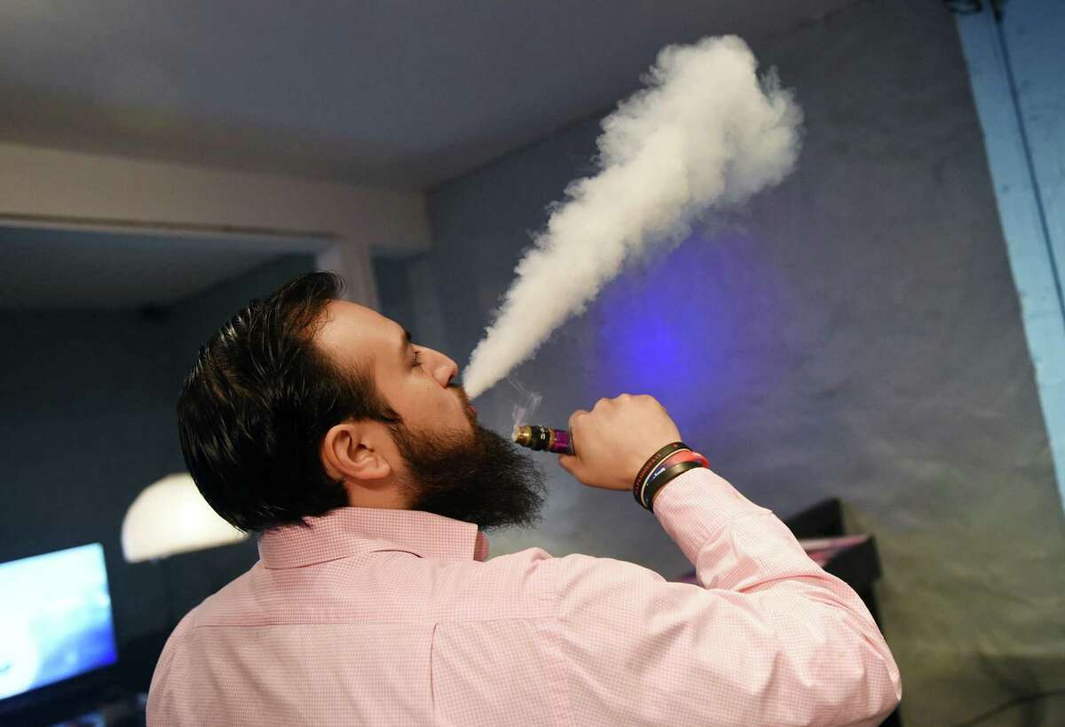 Co-owner Miguel Rivera vapes inside CLOUDS Vapors & Lounge in the Byram section of Greenwich, Conn. Thursday, Feb. 18, 2016. There is propsed legislation for makers of liquid nicotine to childproof their containers, which could be just the start of an effort by Connecticut lawmakers to regulate the electronic cigarette industry and its marketing to kids.