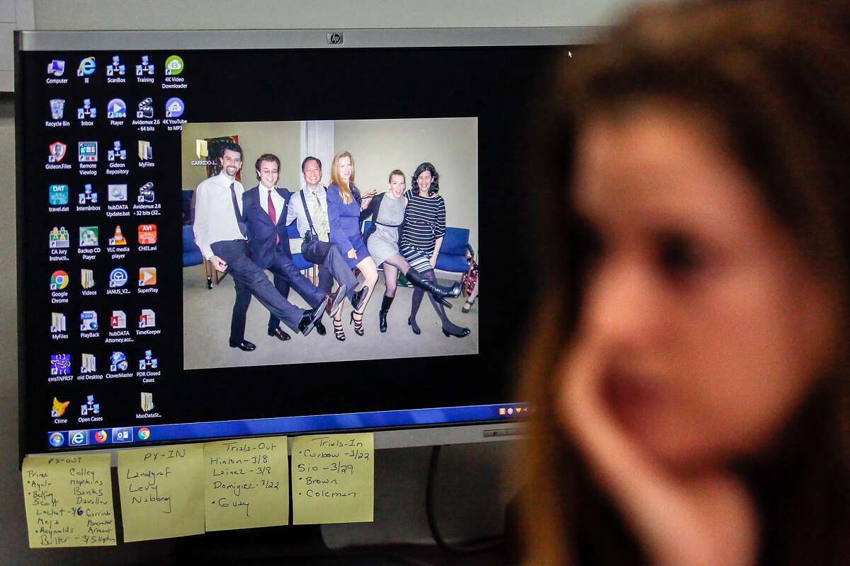 Attorney Elizabeth Hilton's desktop displays a photo of Jeff, her, and other colleagues as she speaks with a reporter at the San Francisco Public Defender's Office on her first day back at work since his boss, Jeff Adachi, died Friday night on Monday, February 25, 2019 in San Francisco, Calif.