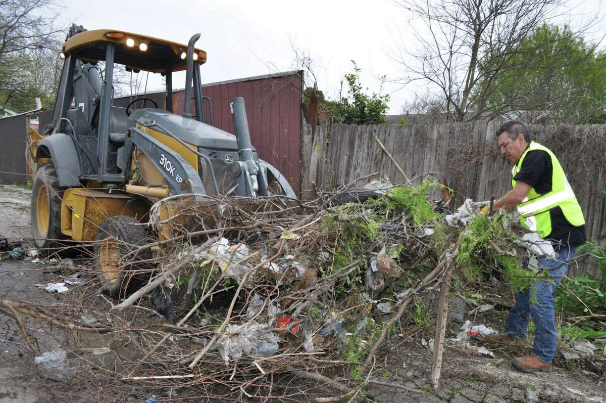 Ruben Alcoser of 5-Star Hauling clears away brush and garbage during a cleanup at The Glen, a neighborhood with chronic trash problems. A long-term solution is needed.