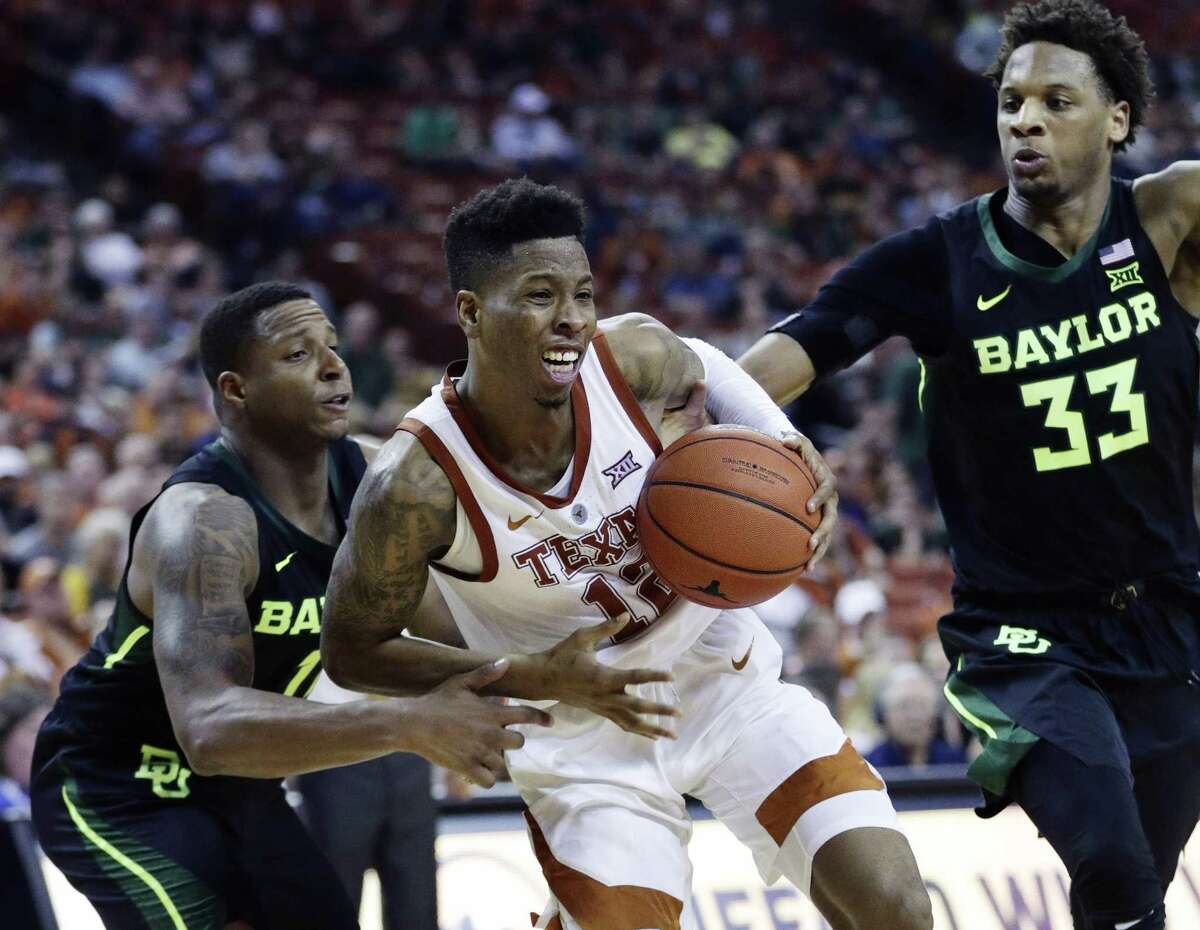 Texas guard Kerwin Roach II (12) drives to the basket between Baylor defenders Mark Vital, left, and Freddie Gillespie (33) during the second half on an NCAA college basketball game, Wednesday, Feb. 6, 2019, in Austin, Texas. (AP Photo/Eric Gay)