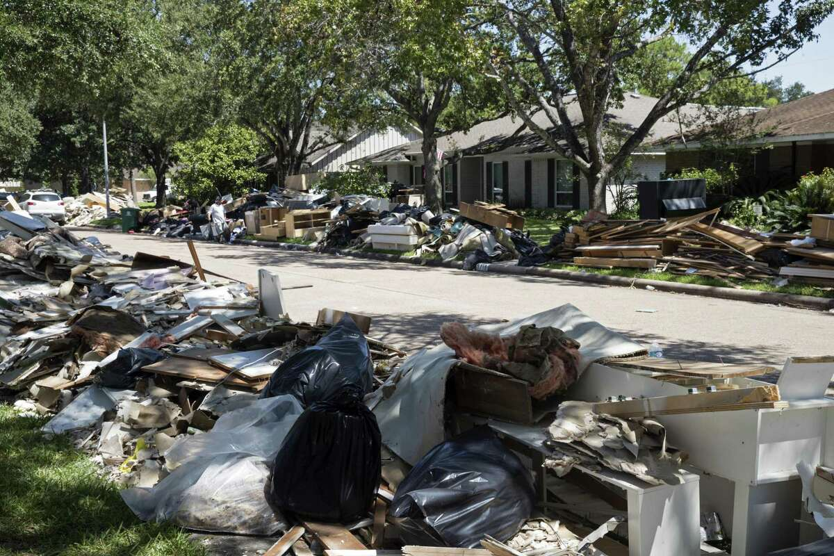 FILE - In this Sept. 7, 2017, file photo, flood damaged debris from homes lines the street in the aftermath of Hurricane Harvey in Houston. Thousands of Houston homeowners still struggling with repairs after Hurricane Harvey hit in 2017 could benefit from up to $400 million in federal grants. The Houston City Council on Wednesday, Jan. 30, 2019, approved contracts with as many as six construction companies for new housing and to fix single-family homes. The funds are from the Department of Housing and Urban Development. (AP Photo/Matt Rourke, File)