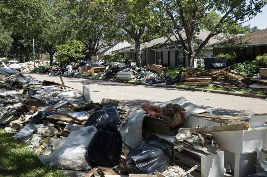 FILE - In this Sept. 7, 2017, file photo, flood damaged debris from homes lines the street in the aftermath of Hurricane Harvey in Houston. Thousands of Houston homeowners still struggling with repairs after Hurricane Harvey hit in 2017 could benefit from up to $400 million in federal grants. The Houston City Council on Wednesday, Jan. 30, 2019, approved contracts with as many as six construction companies for new housing and to fix single-family homes. The funds are from the Department of Housing and Urban Development. (AP Photo/Matt Rourke, File) Photo: Matt Rourke, STF / Associated Press / Copyright 2019 The Associated Press. All rights reserved.
