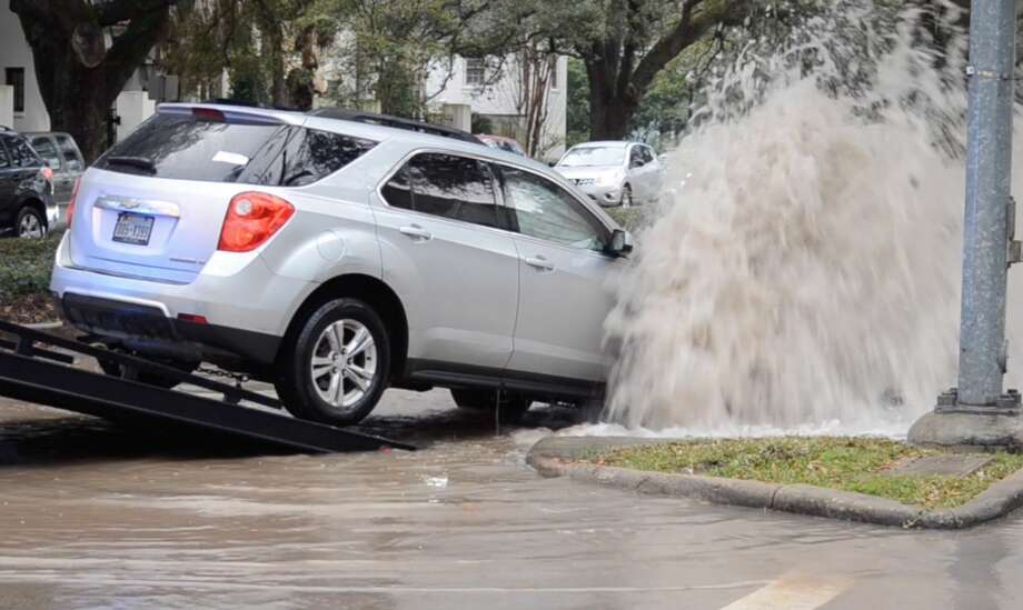 Gusher drenches Rice Village street after car slams into