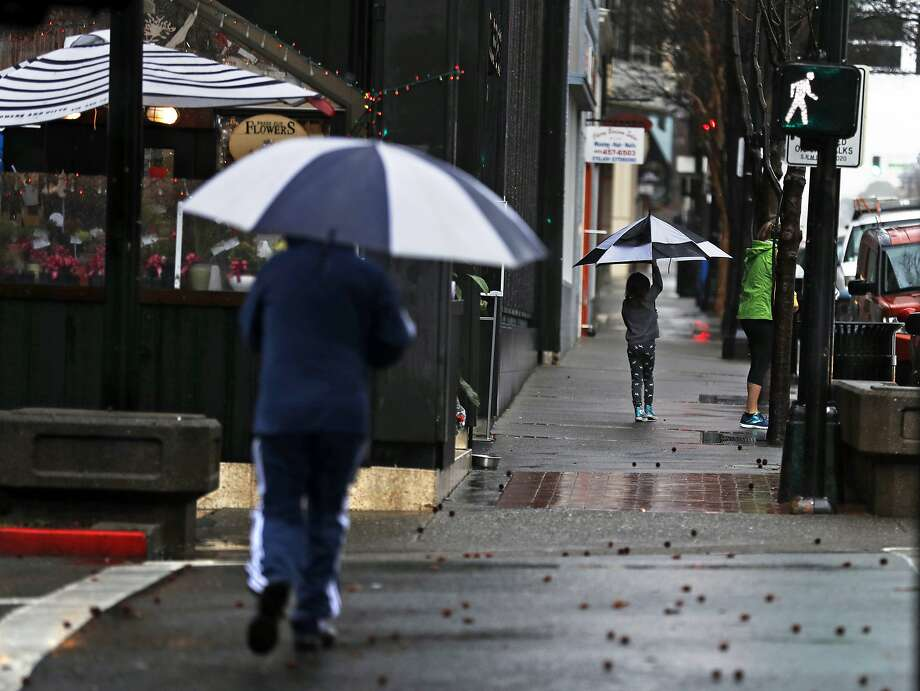 Pedestrians try to avoid the rain on Fourth Street in San Rafael, Calif., on Monday, February 25, 2019. Photo: Scott Strazzante
