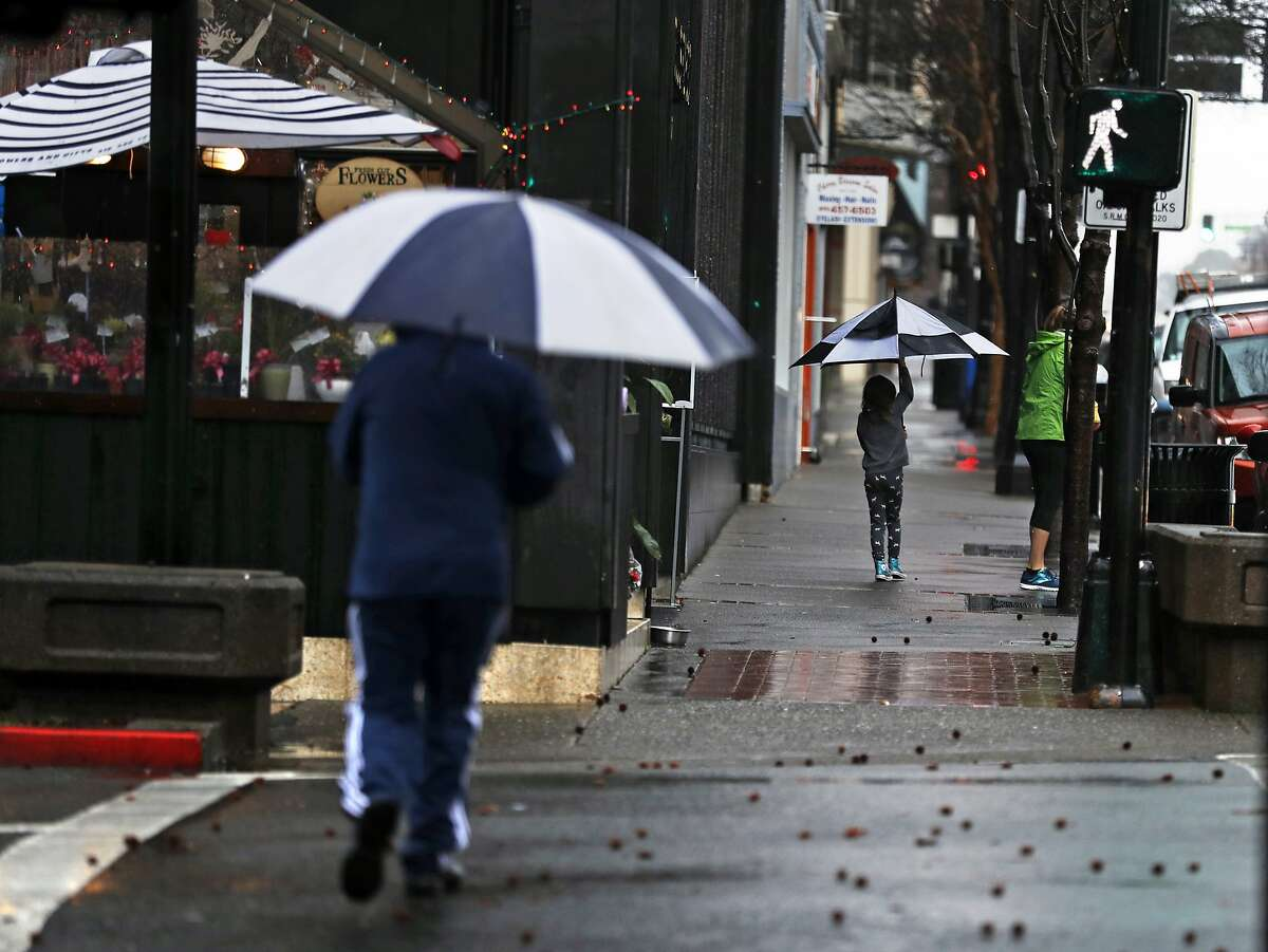 Pedestrians try to avoid the rain on Fourth Street in San Rafael, Calif., on Monday, February 25, 2019.