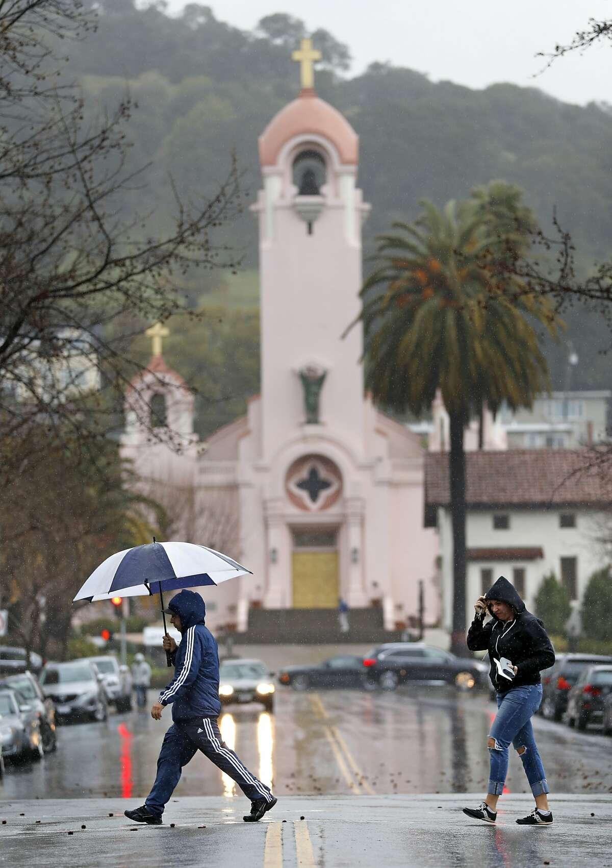 As a steady rain falls, pedestrians cross A Street on Fourth Street in San Rafael, Calif., on Monday, February 25, 2019.