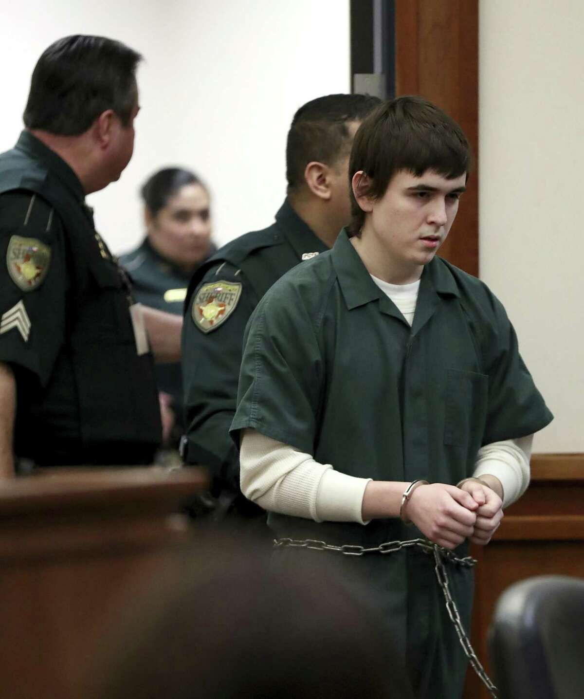 Dimitrios Pagourtzis, the Santa Fe High School student accused of killing 10 people in a May 18 shooting at the high school, is escorted by Galveston County Sheriff's Office deputies into the jury assembly room for a change of venue hearing at the Galveston County Courthouse in Galveston, Texas on Monday, Feb. 25, 2019. The trial of Pagourtzis may be delayed for a year as federal investigators have yet to deliver key evidence, prosecutors said Monday.