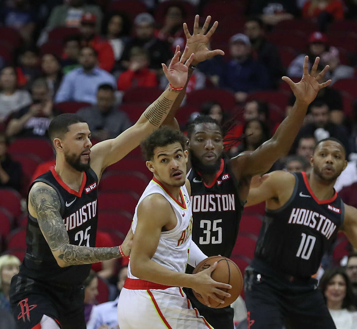Houston Rockets guard Austin Rivers (25), forward Kenneth Faried (35) and guard Eric Gordon (10) stop Atlanta Hawks guard Trae Young (11) during the first half of an NBA basketball game at Toyota Center on Monday, Feb. 25, 2019, in Houston.