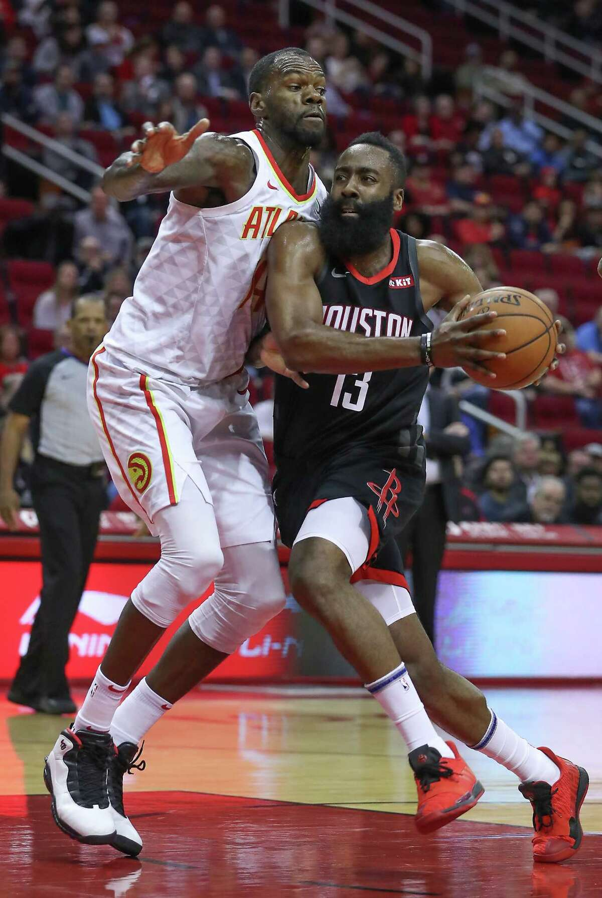Atlanta Hawks center Dewayne Dedmon (14) attempts to stop Houston Rockets guard James Harden (13) from driving to the basket during the first half of an NBA basketball game at Toyota Center on Monday, Feb. 25, 2019, in Houston.