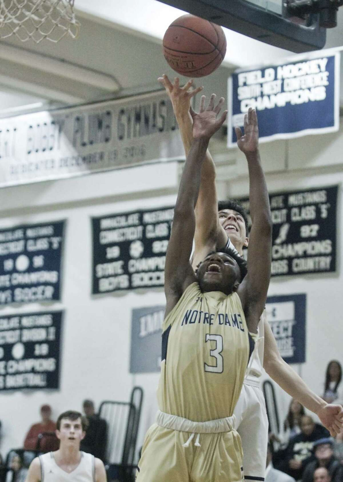 Notre Dame-Fairfield High School's Jonathan Despeignes reaches for the rebound in the SWC boys basketball tournament semifinal against Immaculate High School, played at Immaculate. Monday, Feb. 25, 2019