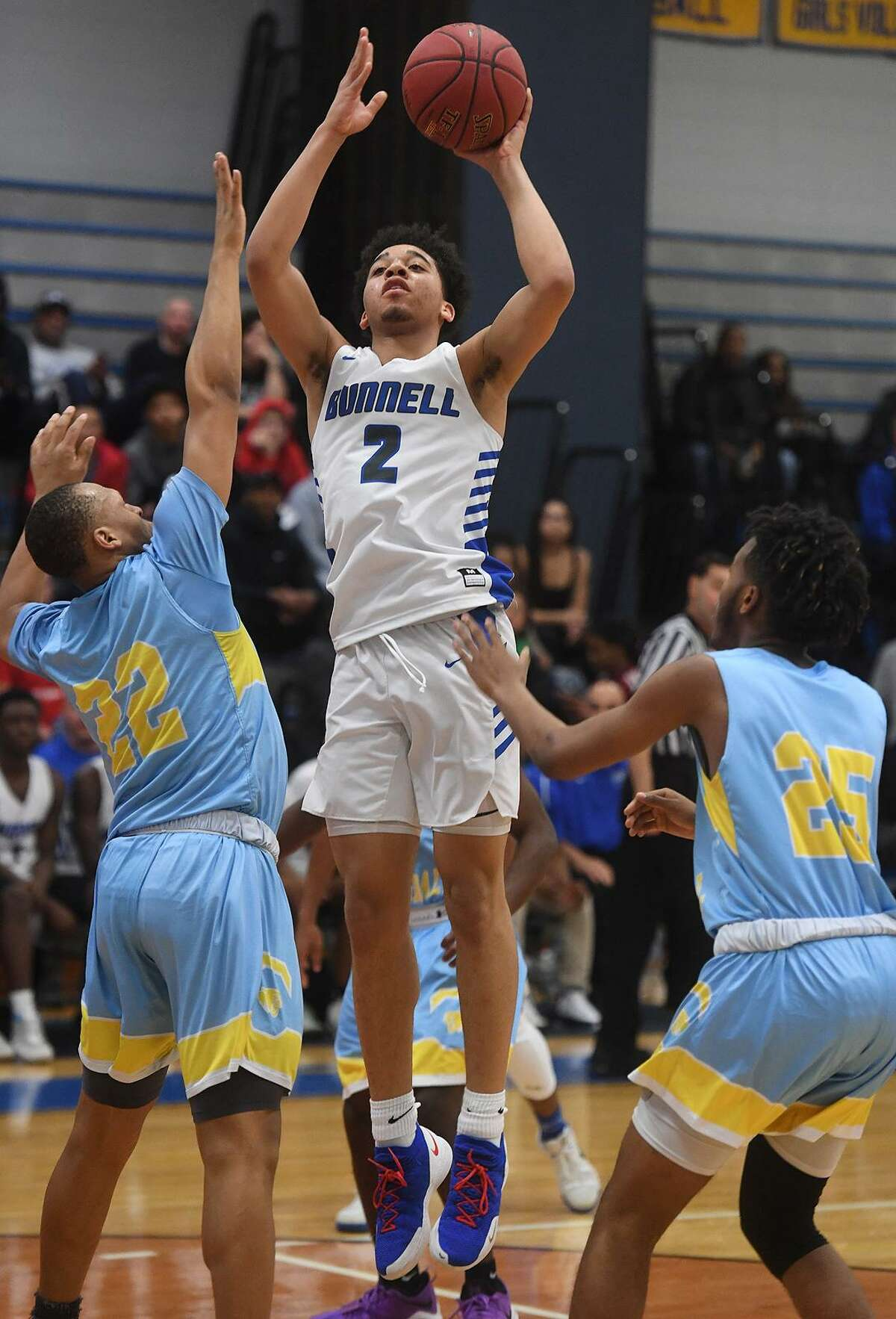 Bunnell's Max Edwards shoots over Kolbe Cathedral defenders Eudell Mason, left, and Jalen Sullivan during the Bulldogs' victory in the SWC boys basketball semifinals at Bunnell High School in Stratford on Monday night.