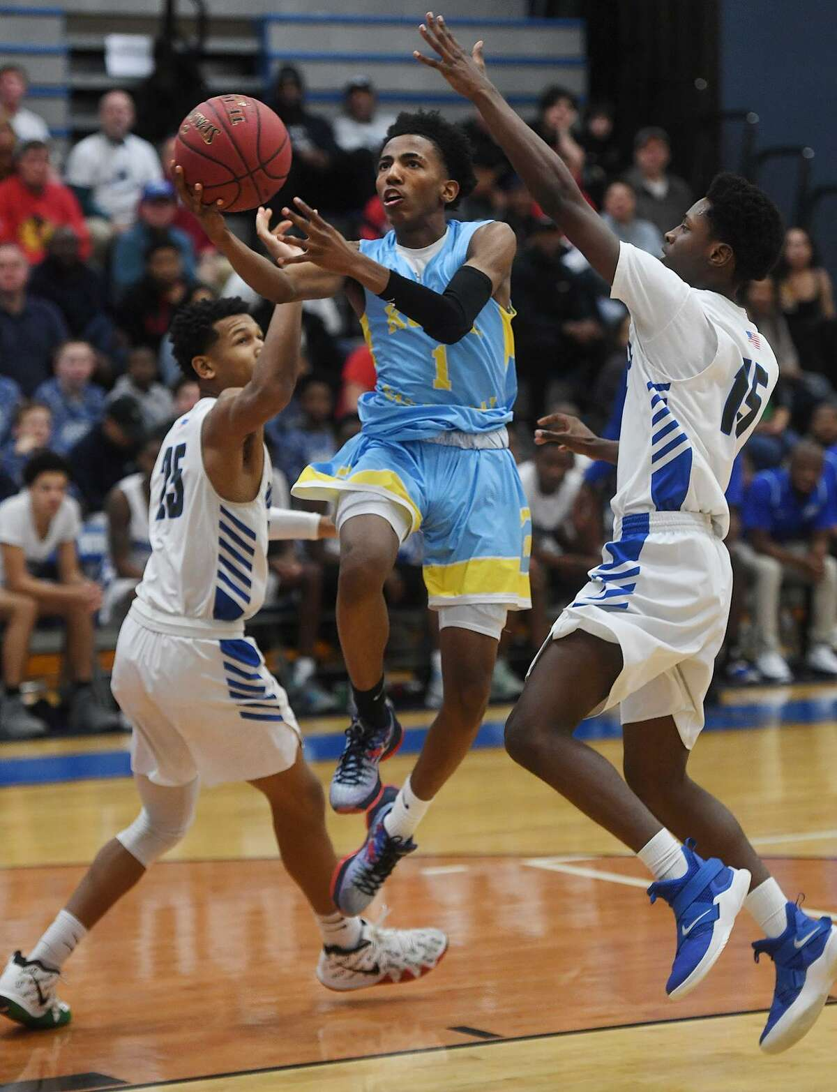 Kolbe Cathedral's Ty Staples-Santos drives to the basket between Bunnell defenders Javon Wilson, left, and Kevin Lanham during Bunnell's victory in the SWC boys basketball semifinals at Bunnell High School in Stratford, Conn. on Monday, February 25, 2019.