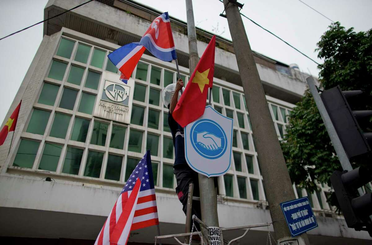 A man installs flags of North Korea, the U.S and Vietnam on a post in a street neighboring Government Guesthouse and the Metropole hotel ahead of the North Korea-U.S. summit in Hanoi, Vietnam, Monday, Feb. 25, 2019. The second summit between U.S President Donald Trump and North Korean leader Kim Jong Un will take place in Hanoi on Feb. 27 and 28. (AP Photo/Gemunu Amarasinghe)