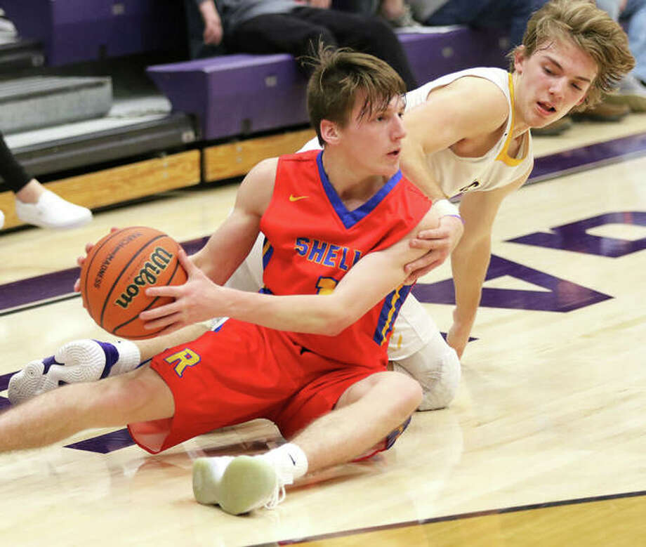Roxana's Andrew Beckman (left) looks for a teammate after going to the floor to reclaim a loose ball ahead of CM's Bryce Zupan in the second half of the Breese Central Class 3A Regional quarterfinal game Monday night in Breese. Photo: Greg Shashack / The Telegraph