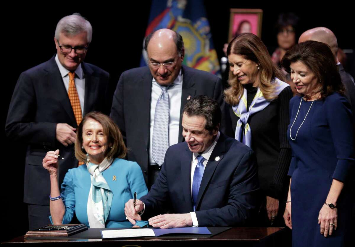 """House Speaker Nancy Pelosi, second from left, joins New York Governor Andrew Cuomo, center, as he signs a gun control bill at a ceremony in New York, Monday, Feb. 25, 2019. Cuomo signed a """"red flag"""" bill, which attempts to prevent people who present a threat to themselves or others from purchasing or owning a gun. (AP Photo/Seth Wenig)"""