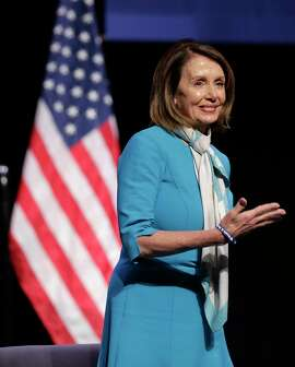 """House Speaker Nancy Pelosi acknowledges the audiences applause while attending a bill signing ceremony in New York, Monday, Feb. 25, 2019. Pelosi joined New York Governor Andrew Cuomo as he signed a """"red flag"""" bill, which attempts to prevent people who present a threat to themselves or others from purchasing or owning a gun. (AP Photo/Seth Wenig)"""