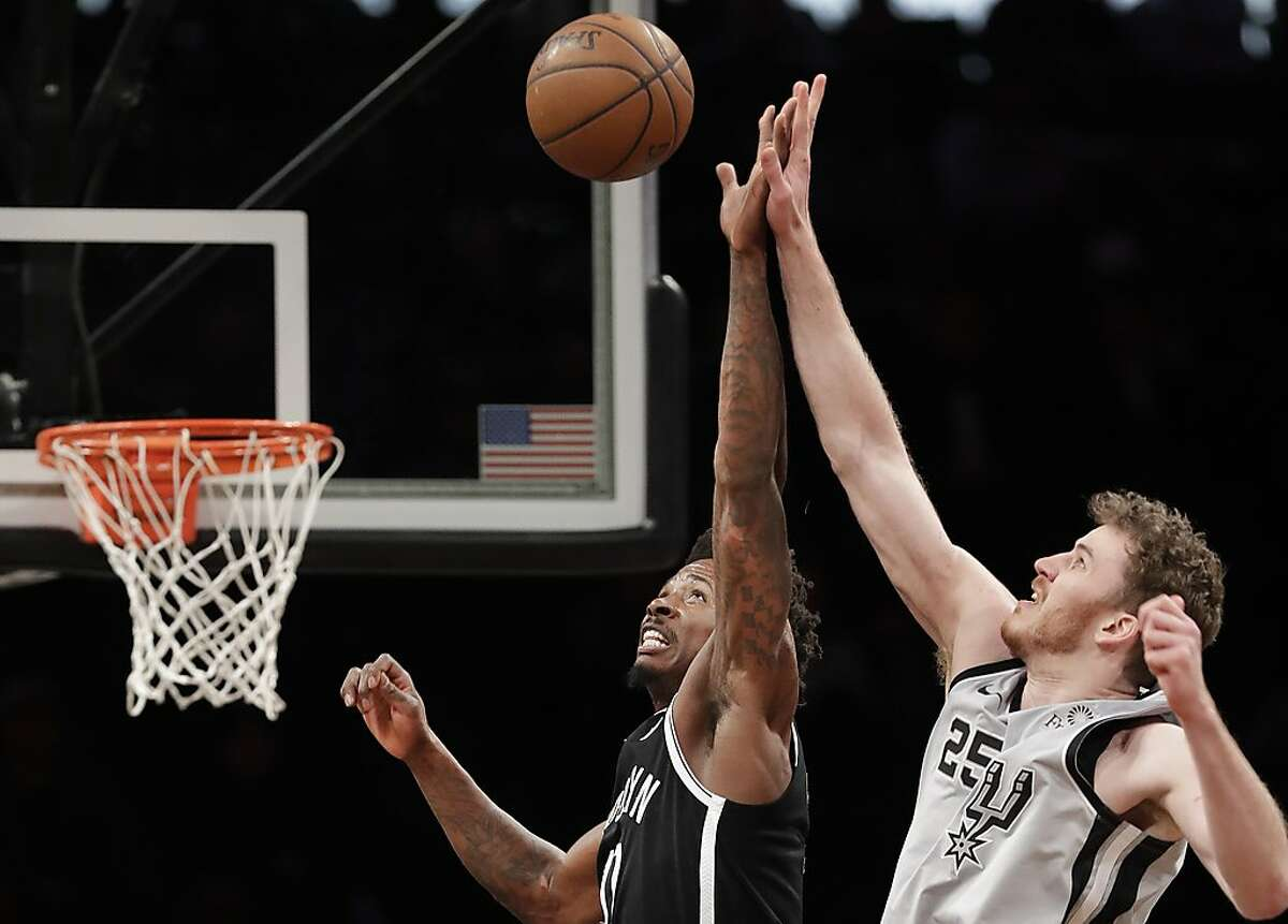 Brooklyn Nets forward Ed Davis, left, tries to tip the ball away from San Antonio Spurs center Jakob Poeltl (25) during the second half of an NBA basketball game, Monday, Feb. 25, 2019, in New York. (AP Photo/Kathy Willens)