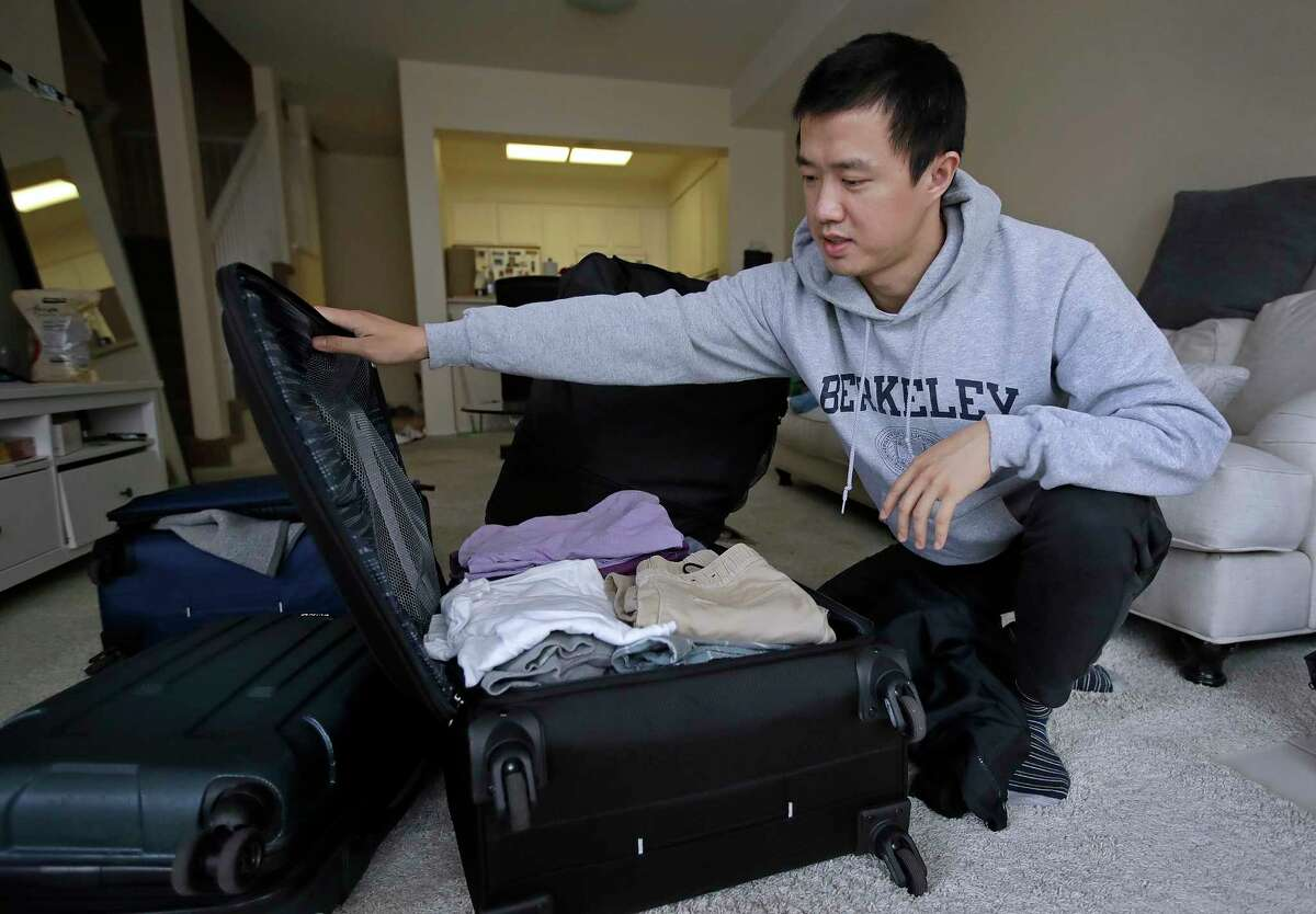 """In this Monday, Feb. 4, 2019, photo, Leo Wang packs a suitcase at his home in San Jose, Calif. Wang has found himself trapped in an obstacle course regarding H-1B work visas for foreigners. His visa denied and his days in the United States numbered, Wang is looking for work outside the country. ?""""I still believe in the American dream,?"""" he says. ?""""It?'s just that I personally have to pursue it somewhere else.?"""" (AP Photo/Ben Margot)"""